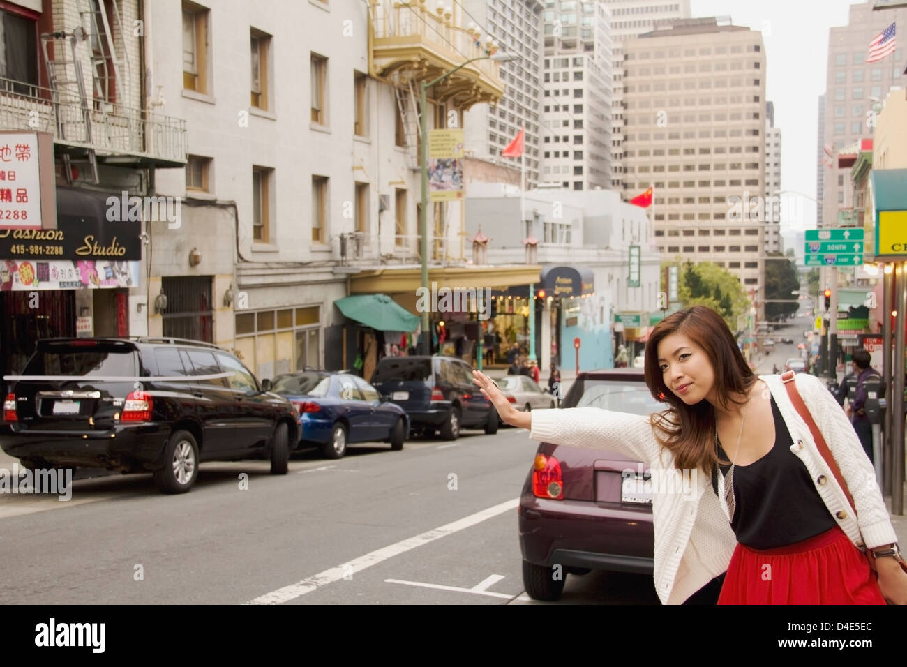 A woman on the side of the road hailing a cab; san francisco california united states of america - Stock Image