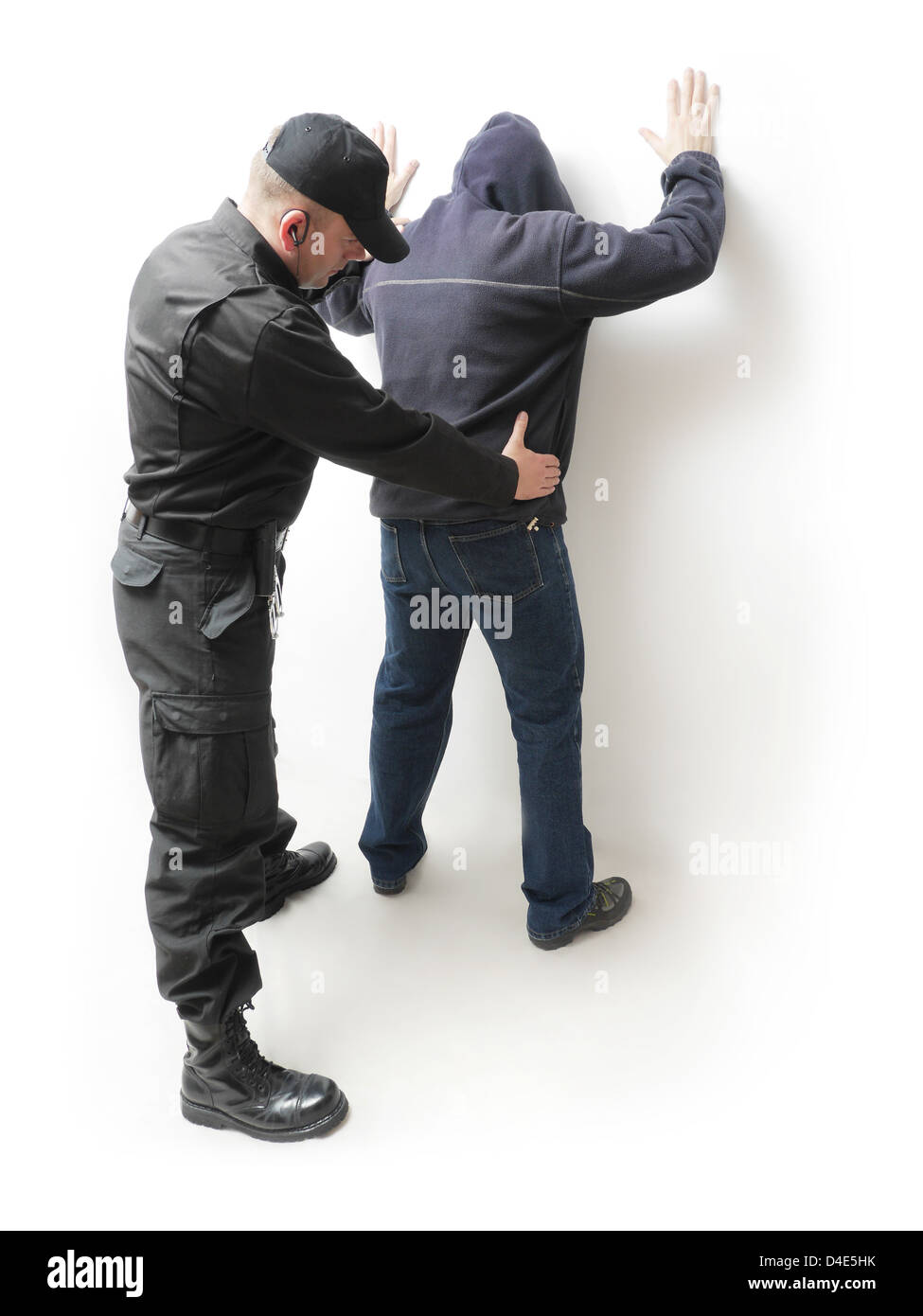 Man being searched by a policeman in black uniform - Stock Image