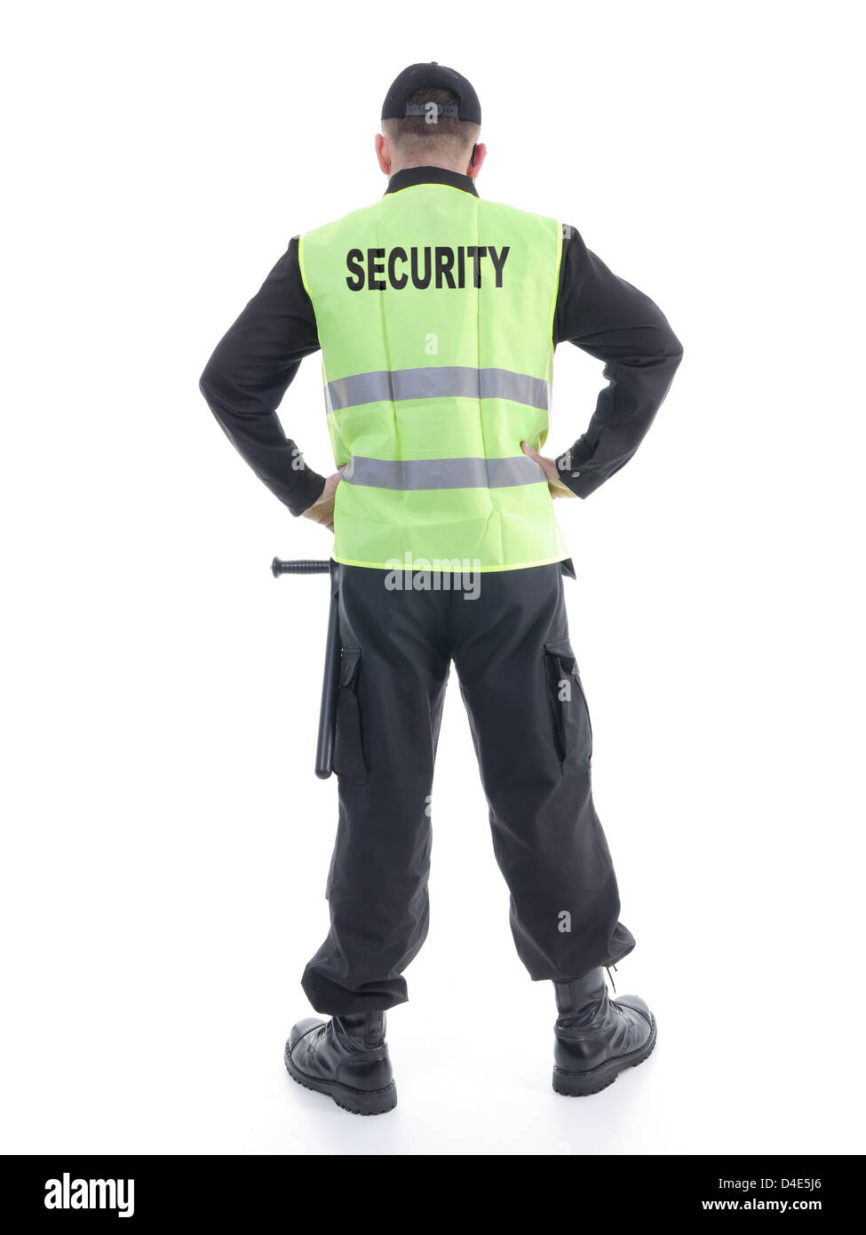 Security man wearing black uniform and yellow reflective vest standing confidently with arms resting on hips, facing Stock Photo