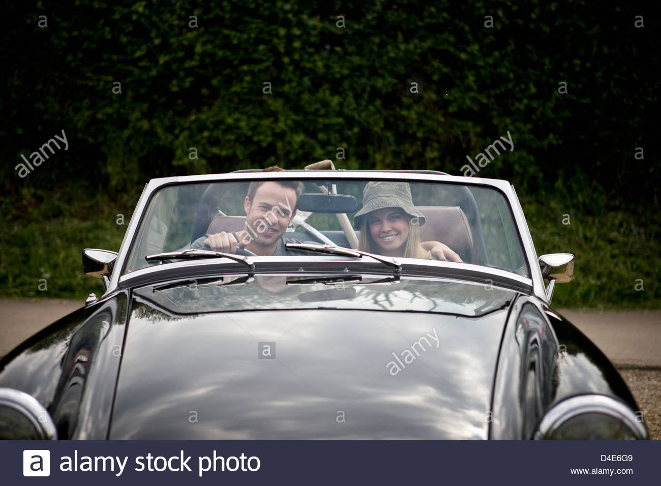 A young couple driving a black sports car with gardening tools in the back - Stock Image