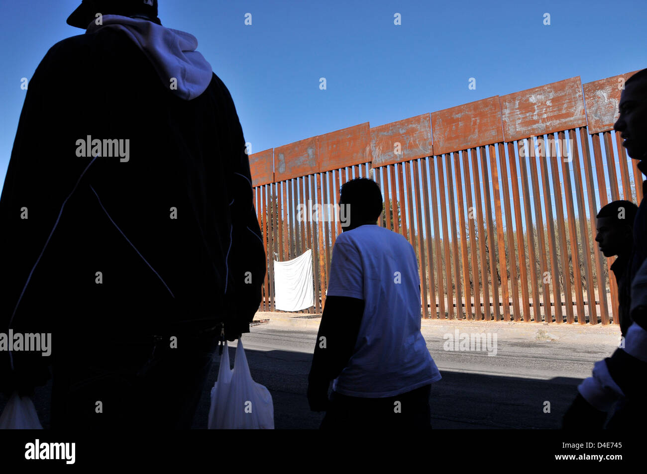 Men in Mexico, pass the border wall where a US Border Patrol agent in Nogales, Arizona, USA, shot a youth in Mexico. - Stock Image