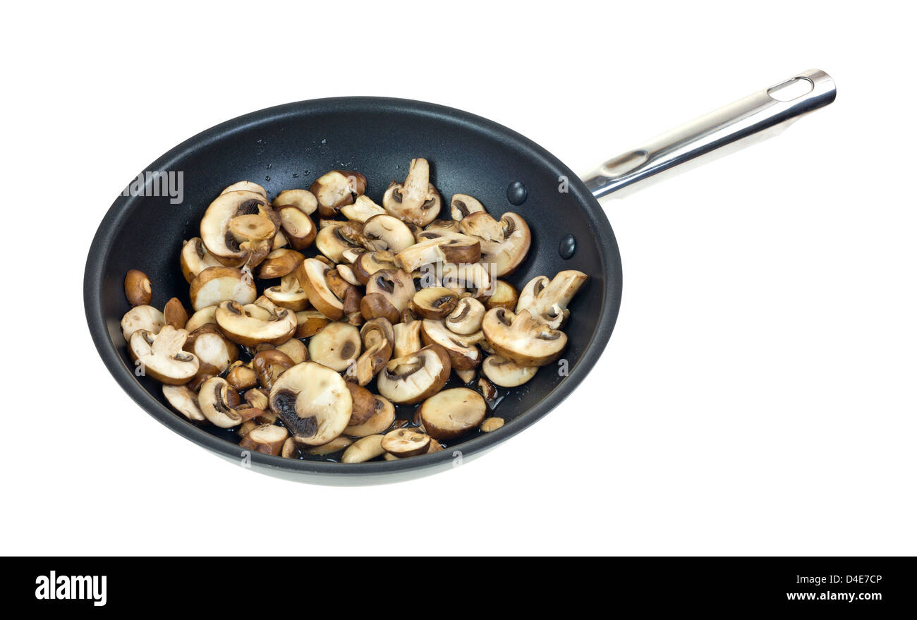 A large amount of sliced mushrooms cooking in olive oil in a large skillet on a white background. - Stock Image