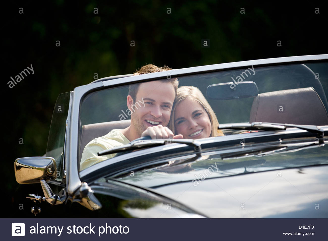 A young couple driving a black sports car - Stock Image