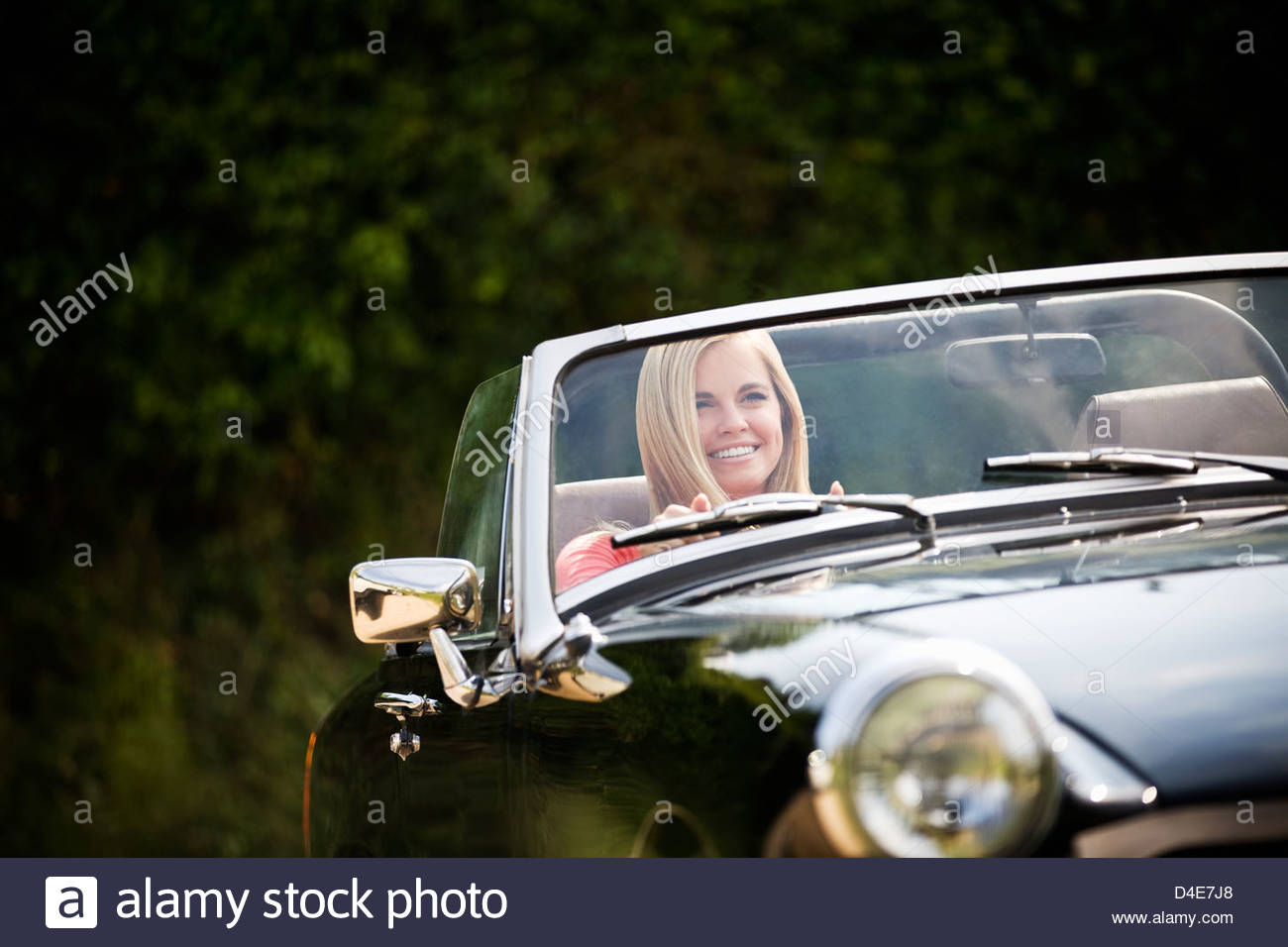 A young woman driving a black sports car - Stock Image