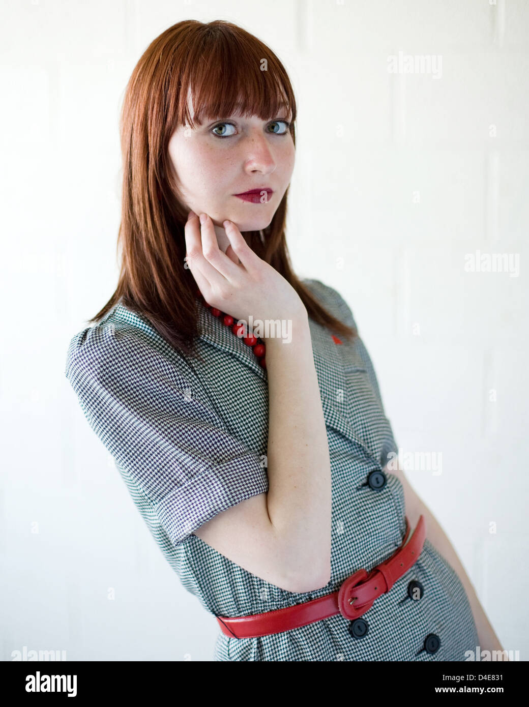 Young red haired woman wearing a retro styled suit - Stock Image