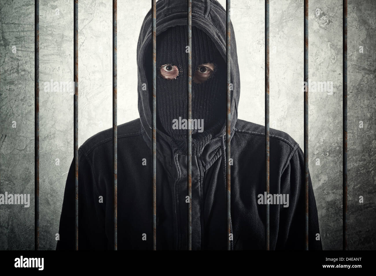 Arrested burglar concept, thief with balaclava caught and arrested, put behind bars - Stock Image