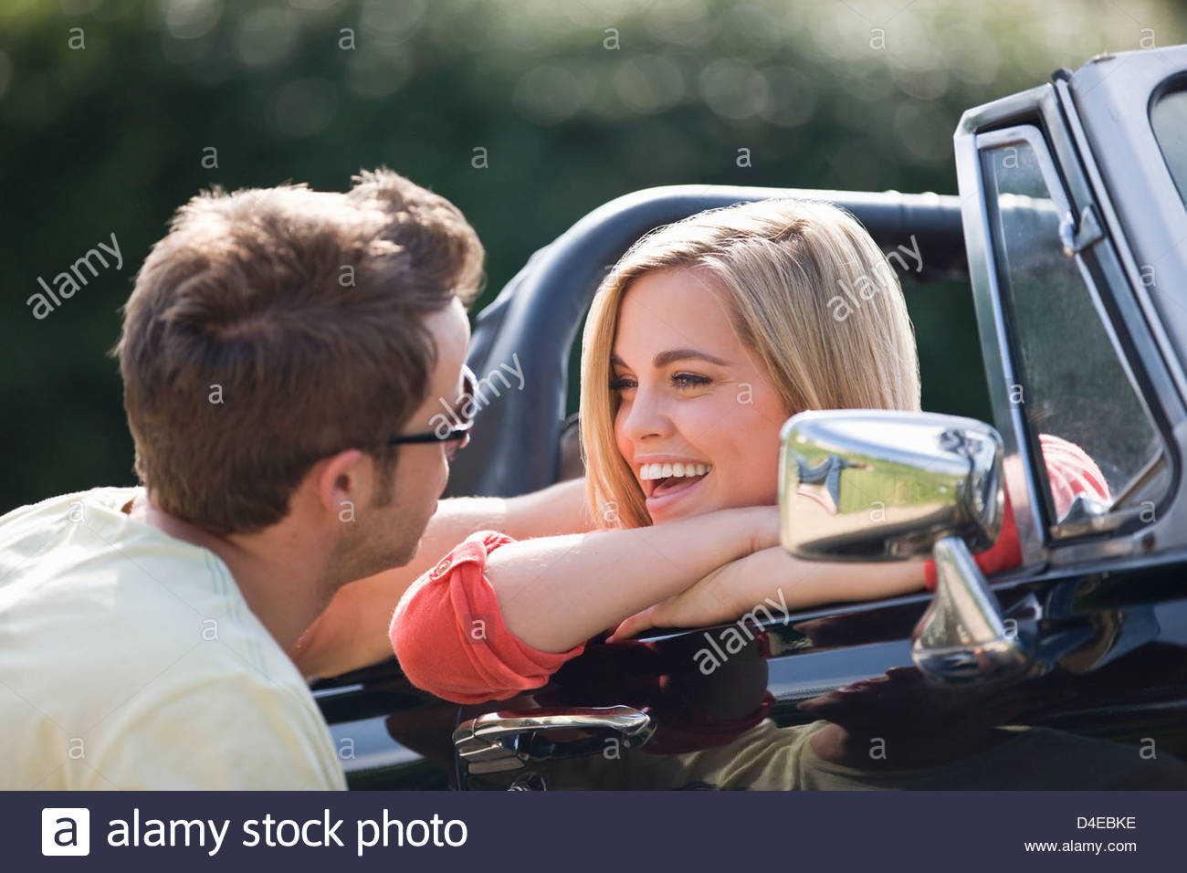 A young man speaking to a young woman in a black sports car - Stock Image
