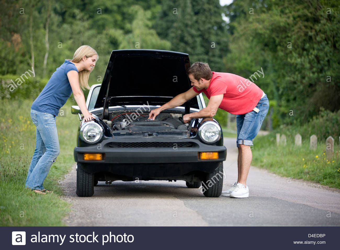 A young couple standing next to their broken down sports car, man looking at the car engine - Stock Image