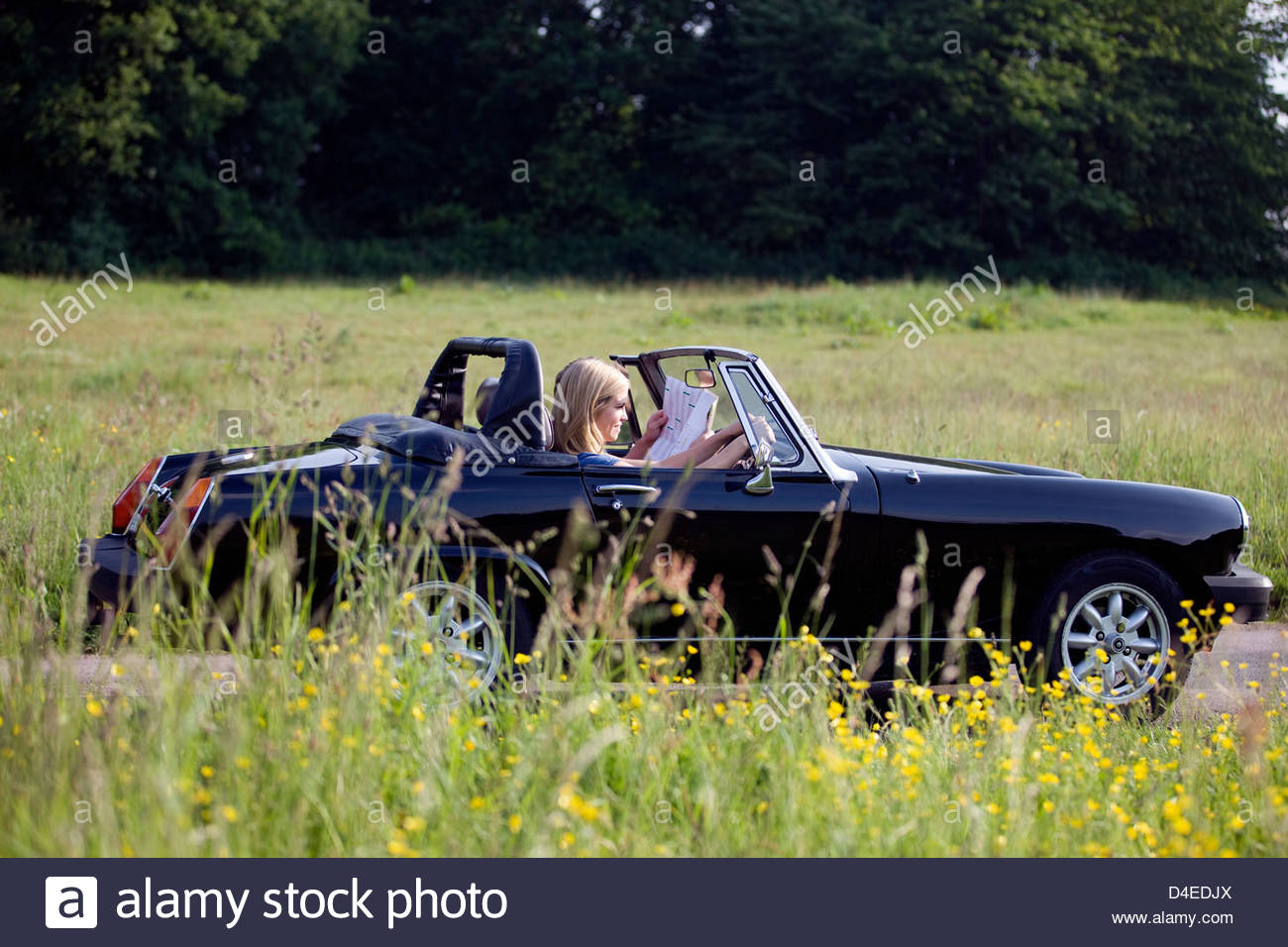 A young couple driving in the countryside, man looking at a road map - Stock Image
