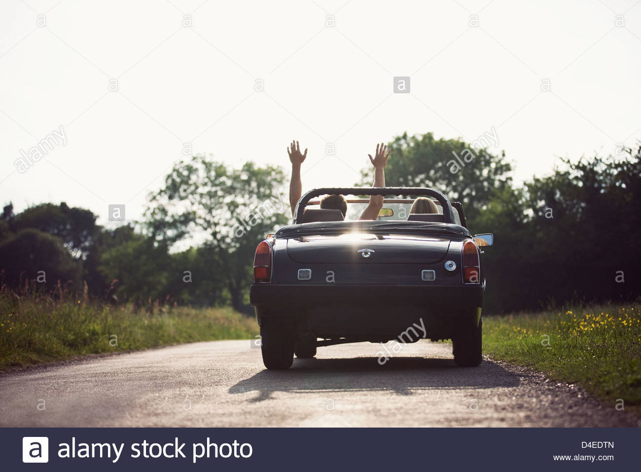 A young couple driving in a convertible black sports car, man with his arms in the air - Stock Image