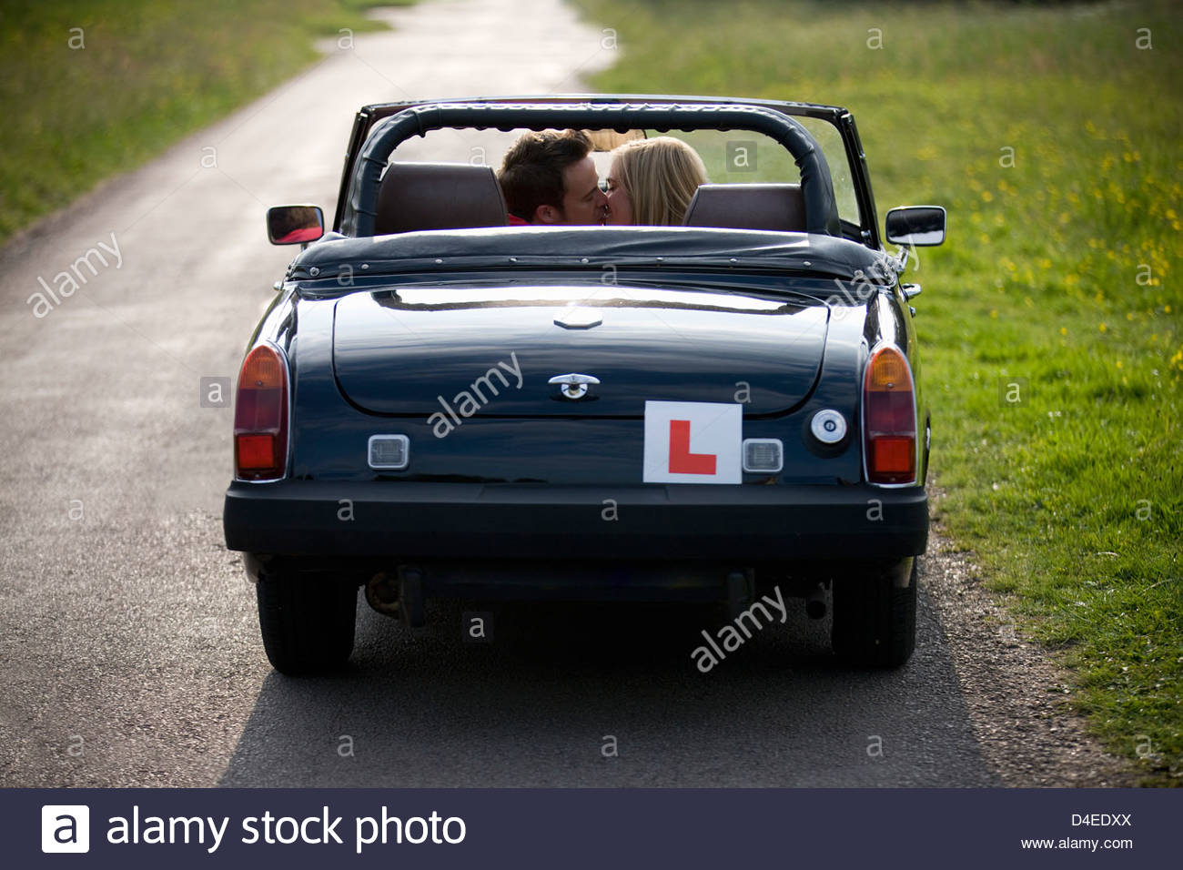 A young couple in a black sports car kissing, rear view Stock Photo