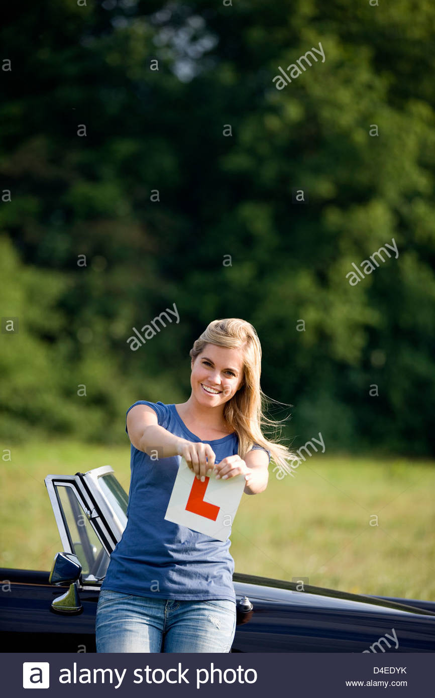 A young woman standing in front of a black sports car, tearing up an L Plate - Stock Image