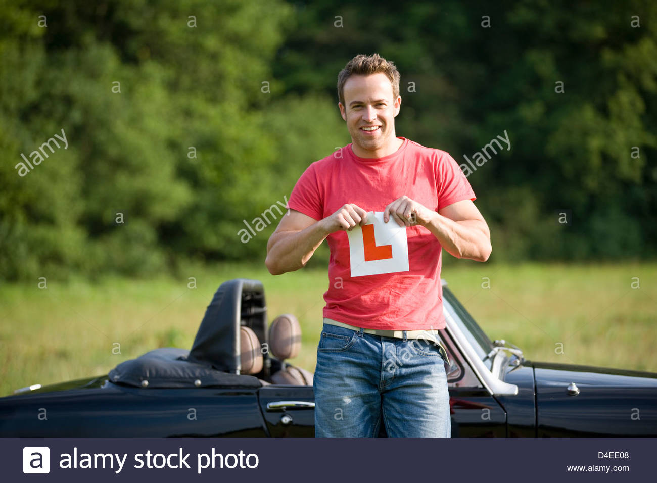 A young man standing in front of a black sports car, tearing up an L Plate - Stock Image