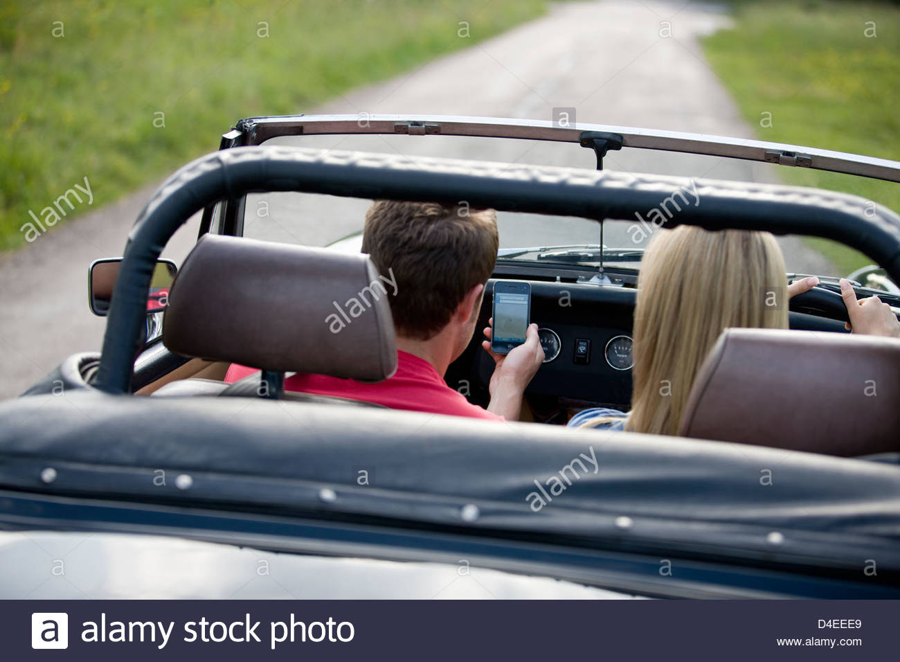 A young couple driving in the countryside, man looking navigating using a smartphone Stock Photo
