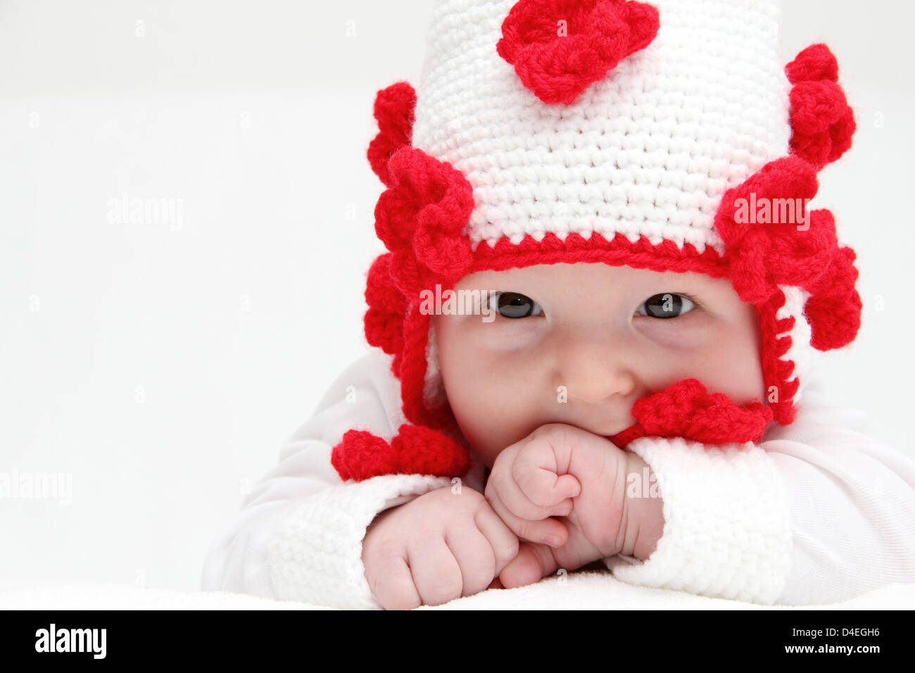 Little baby with knitted white hat baby on stomach - Stock Image