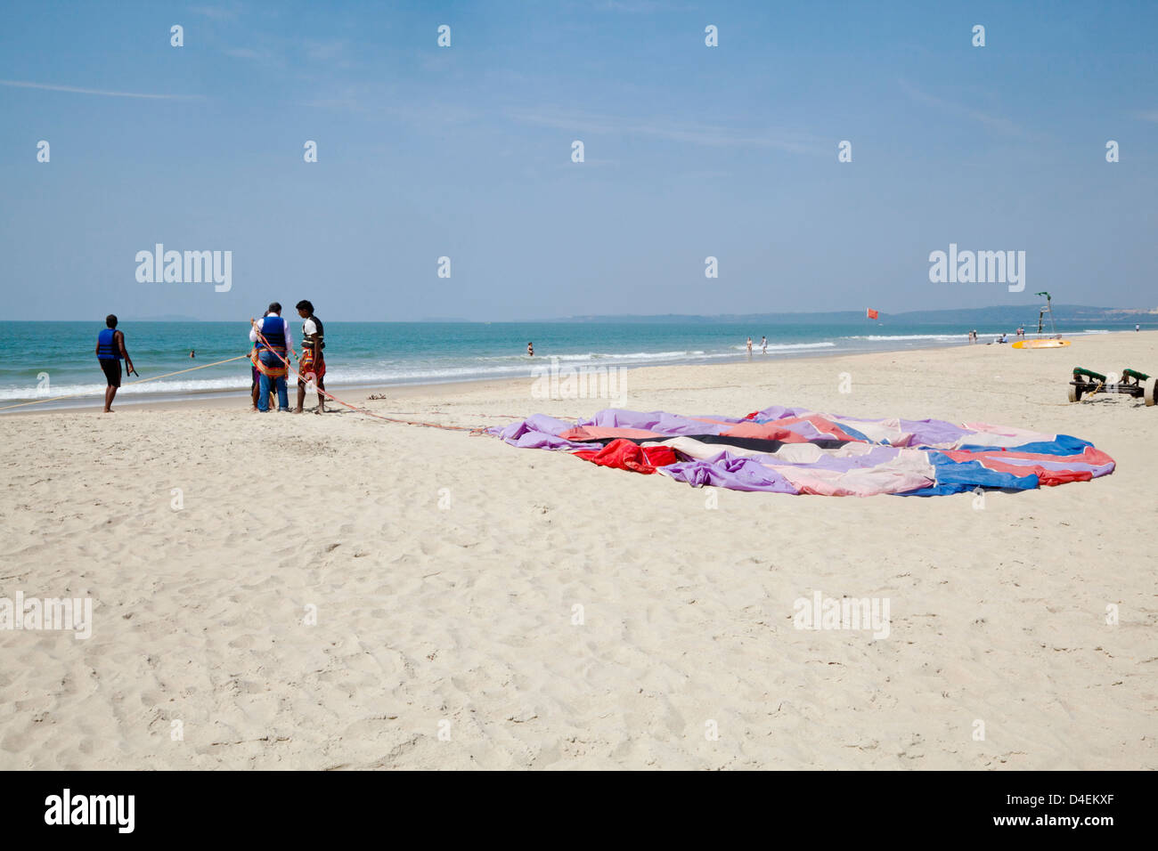 Concept, getting ready for paragliding over the sandy shoreline on beach parachute laid flat on ground Stock Photo