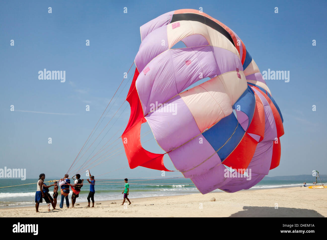 Workers getting a customer ready for para gliding over the sandy shoreline on a secluded beach patrolled by lifeguards - Stock Image