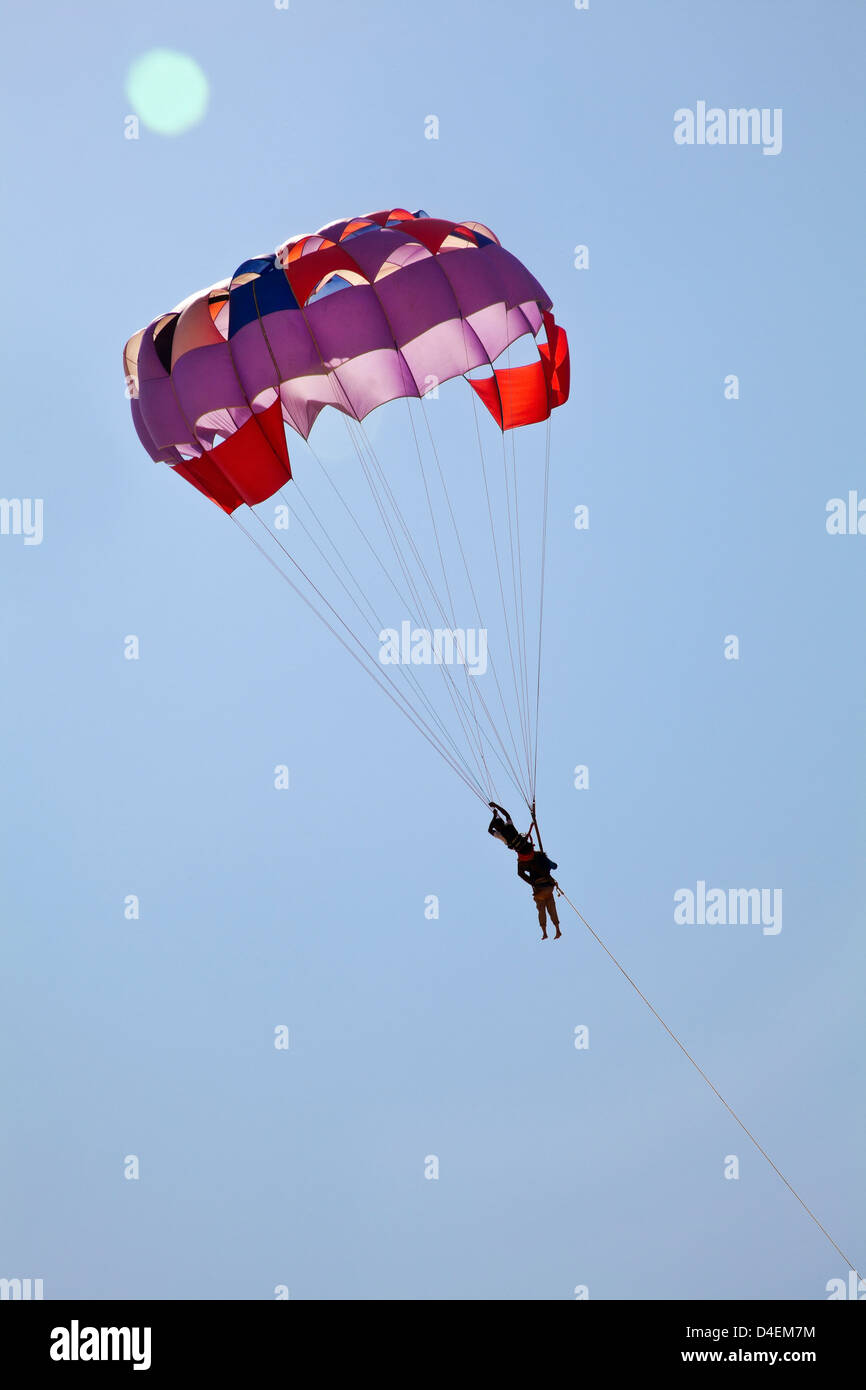 vertical portrait of a couple paragliding in a clear blue sky and sunlight creating lens flare. Generic shot take Stock Photo