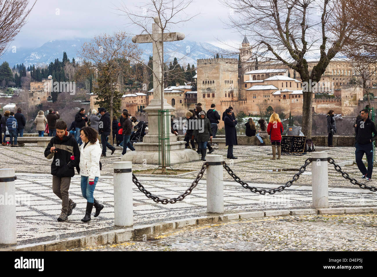 Tourists at San Nicolas square and viewpoint with Alhambra palace in background. Granada, Spain - Stock Image