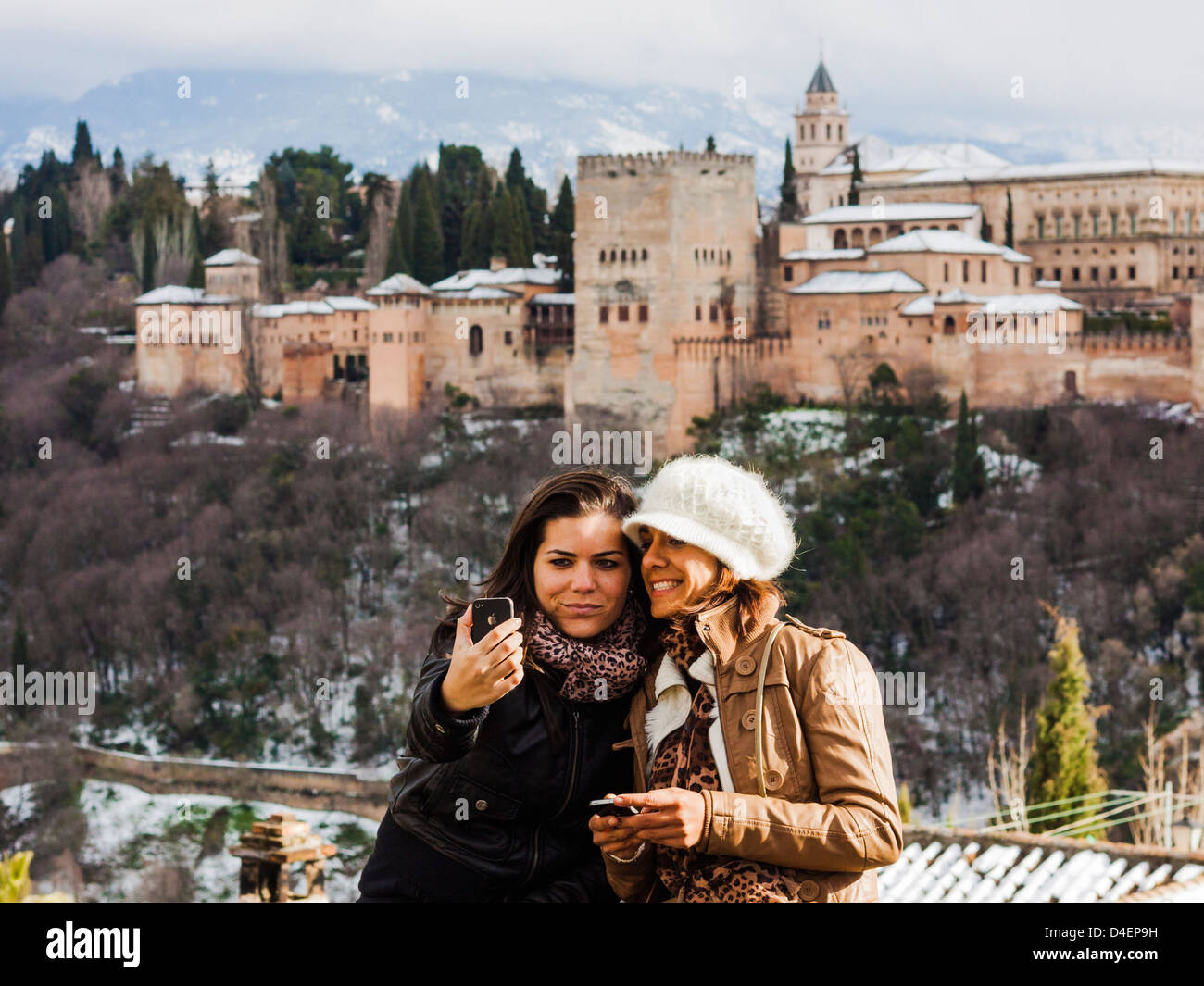Two female tourist friends taking a selfie with a cellphone camera and snowcapped Alhambra palace in Background. - Stock Image