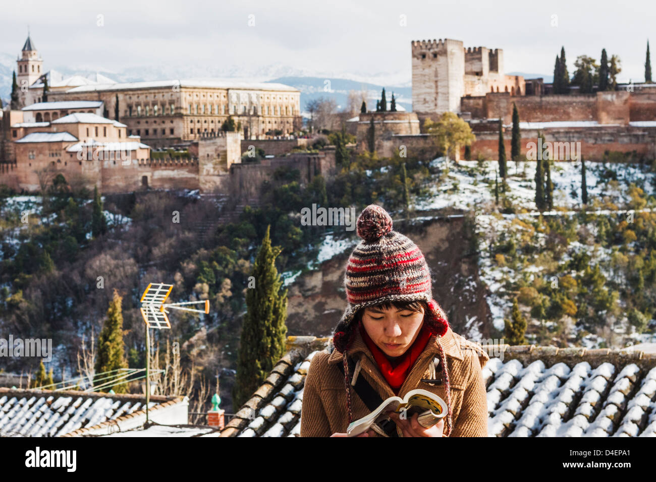 Female Japanese tourist reading a guidebook with snowcapped Alhambra palace in background. Granada, Spain - Stock Image