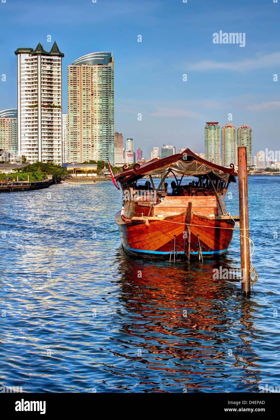 Reflection of the old against the backdrop of the new / Rice Barge on the Chao Phraya River / Bangkok - Stock Image