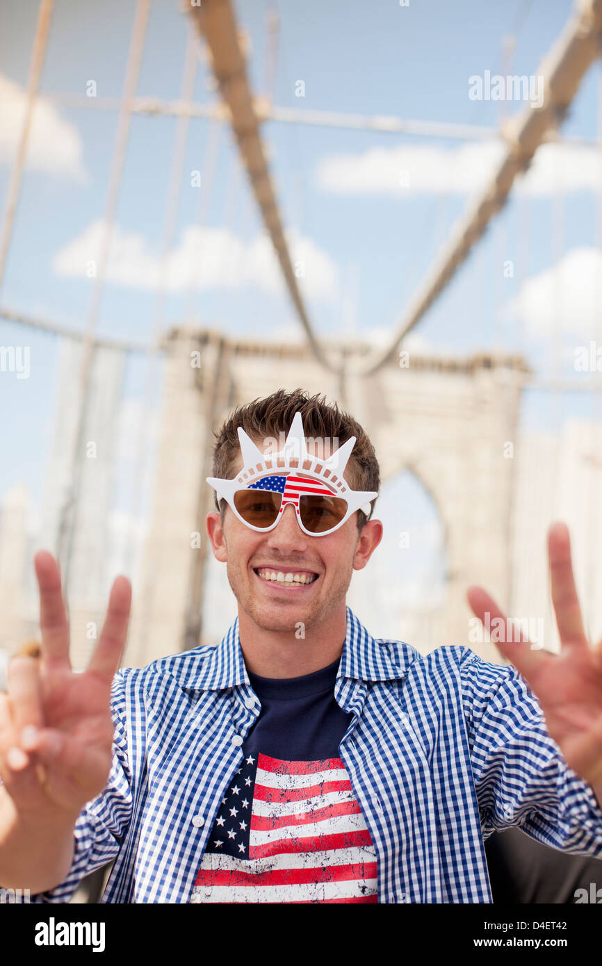 Man in novelty sunglasses on urban bridge - Stock Image