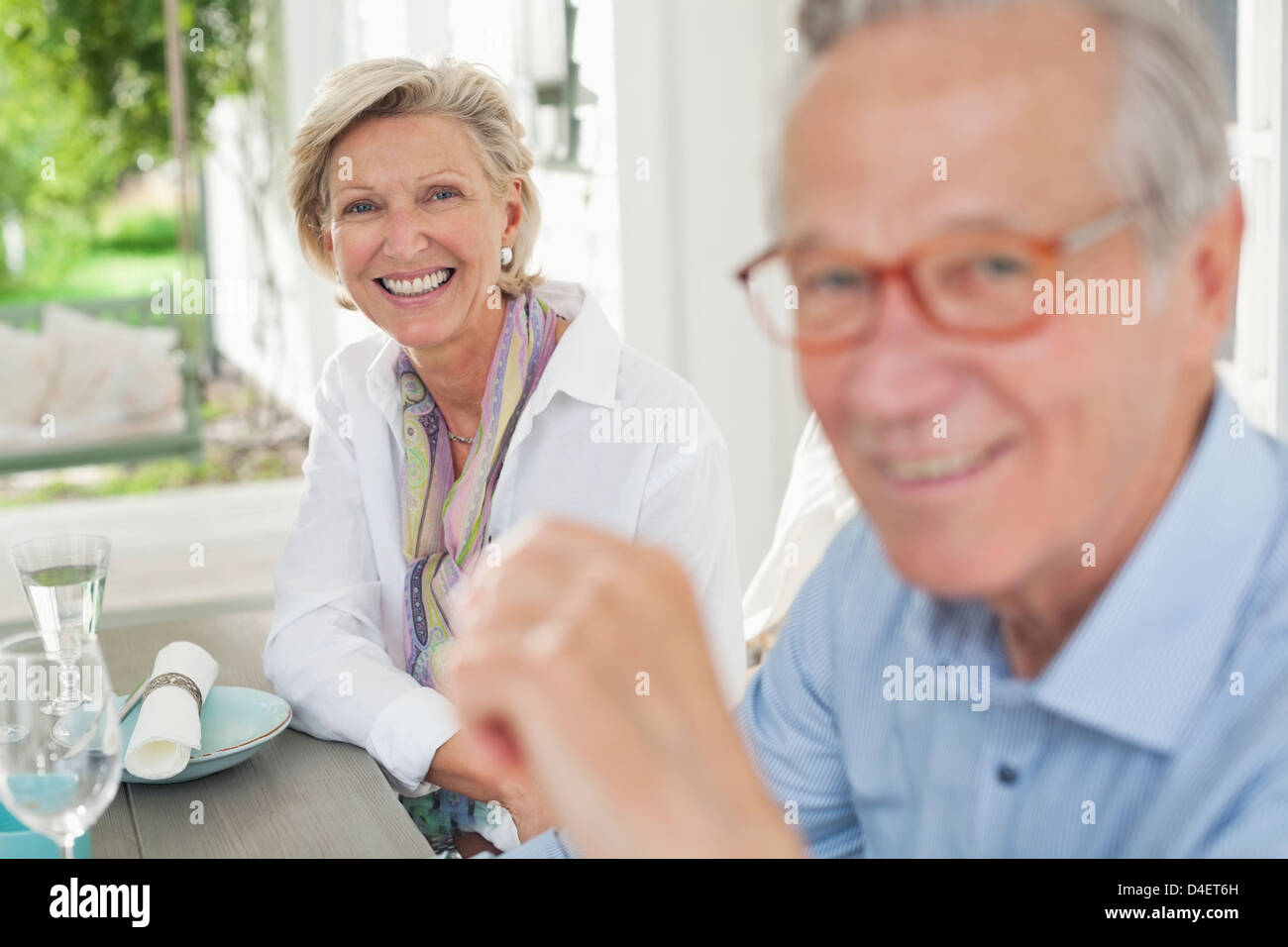 Couple smiling together at table - Stock Image