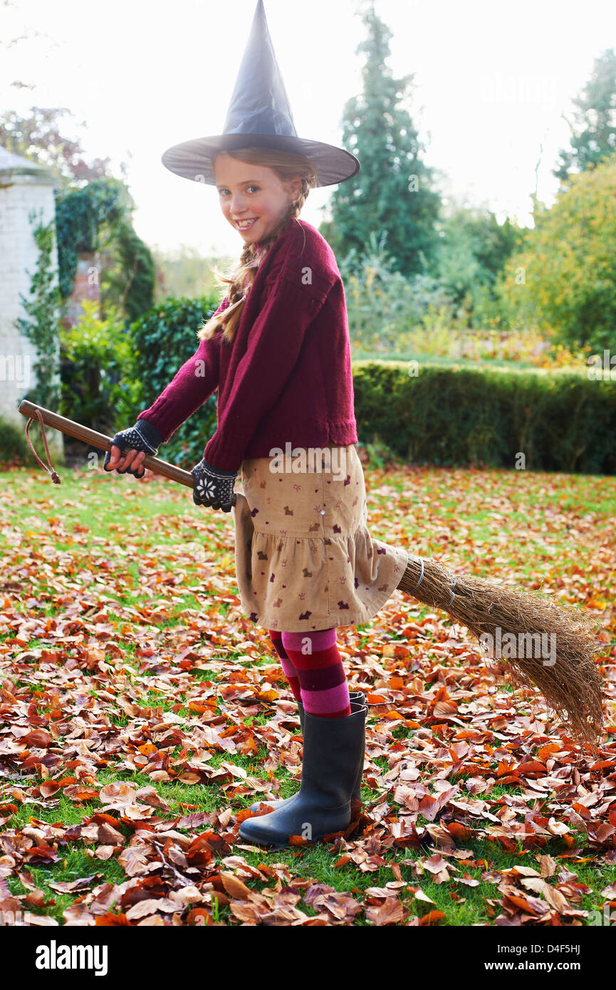 Girl wearing witch costume on broom outdoors - Stock Image