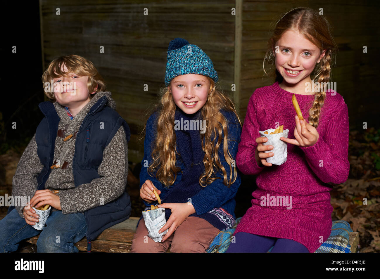 Smiling children eating french fries at night - Stock Image