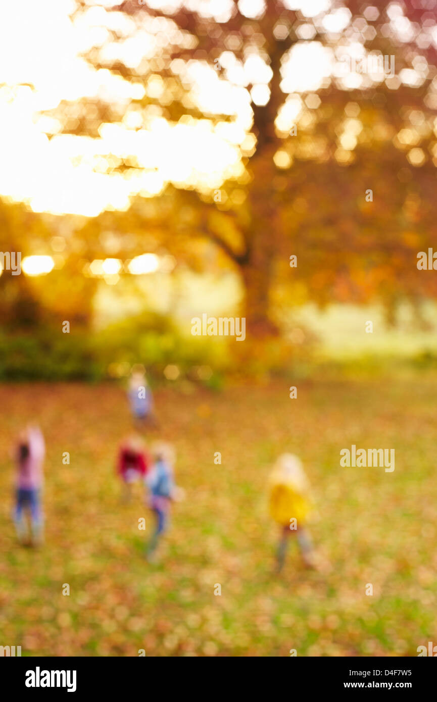 Blurred view of children in field - Stock Image