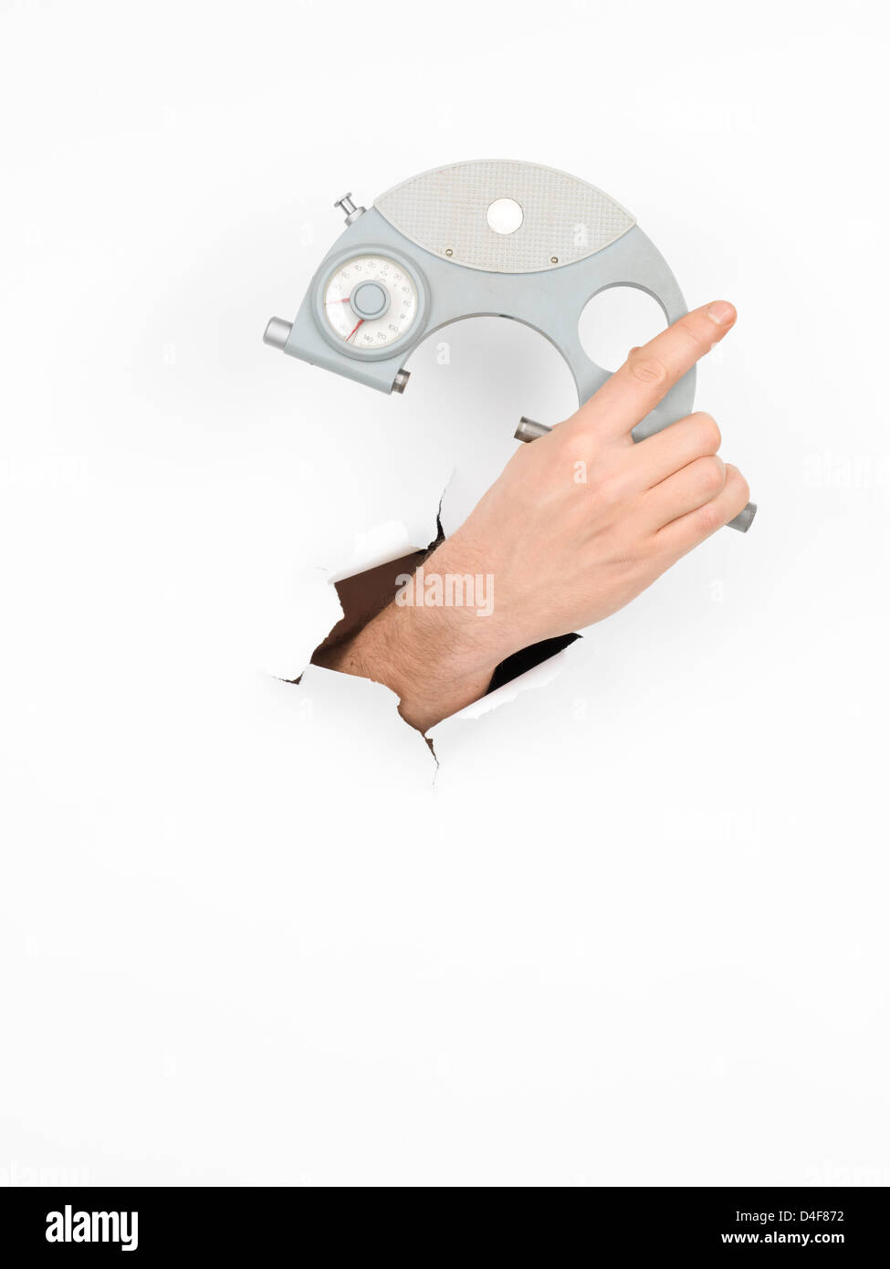 close-up of male hand holding a micrometer through a torn white paper, isolated - Stock Image
