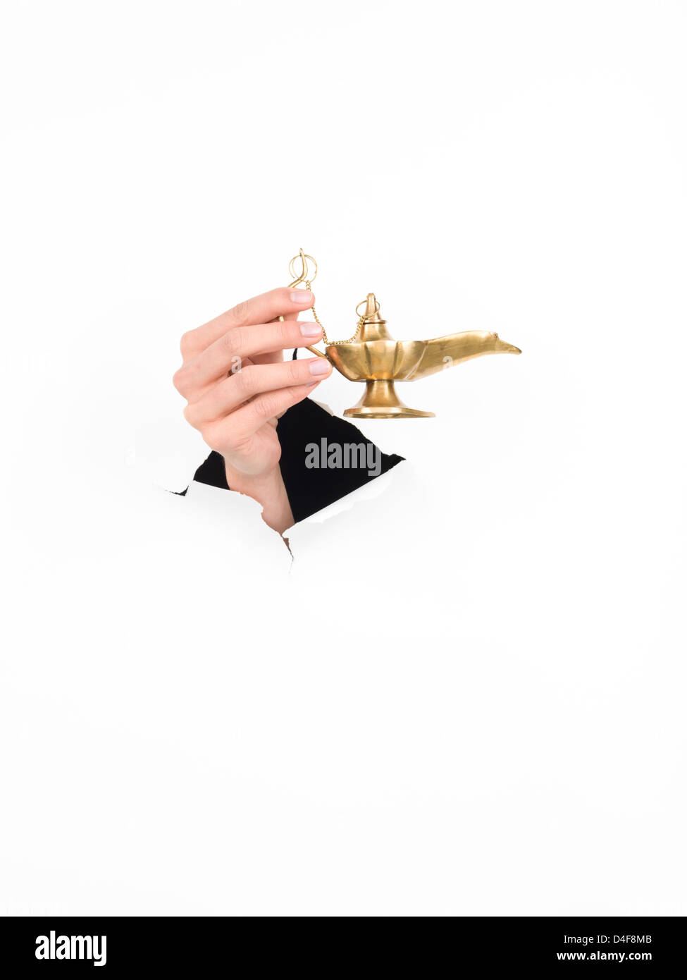 close-up of female hand holding a magic lamp through a torn white paper, isolated - Stock Image
