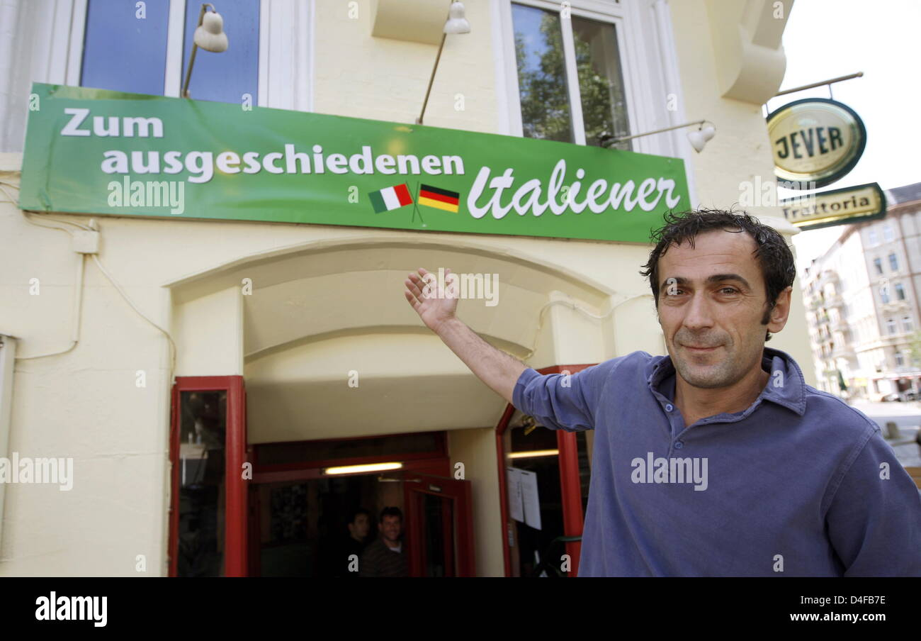 Restaurant owner Remo points at the new name sign of his pizzeria 'Zum ausgeschiedenen Italiener' (Literally: - Stock Image