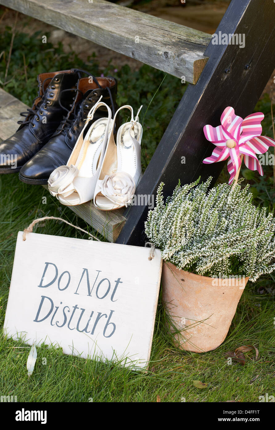 Newlywed couple's shoes with 'do not disturb' sign - Stock Image