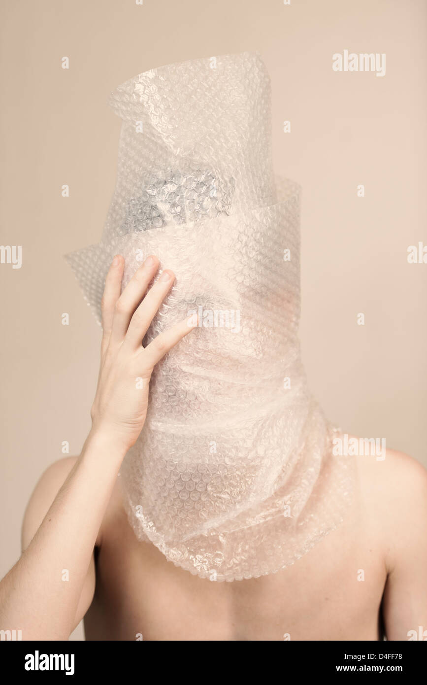 Portrait of anxious young man wrapped in plastic. He is looking sad, shy and discontent. - Stock Image