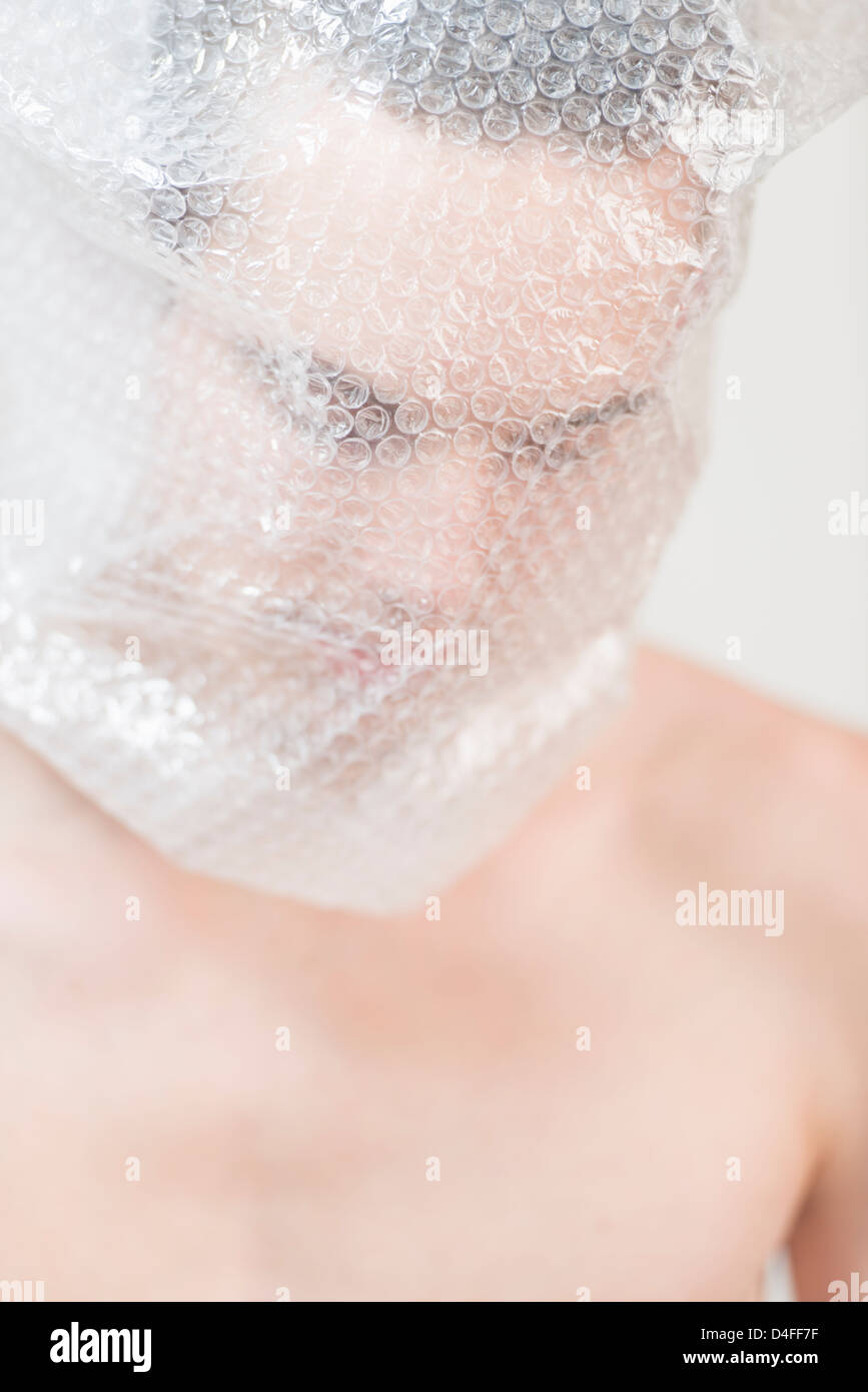 Portrait of anxious young adult male wrapped in transparent plastic. He is looking sad, shy and discontent. - Stock Image