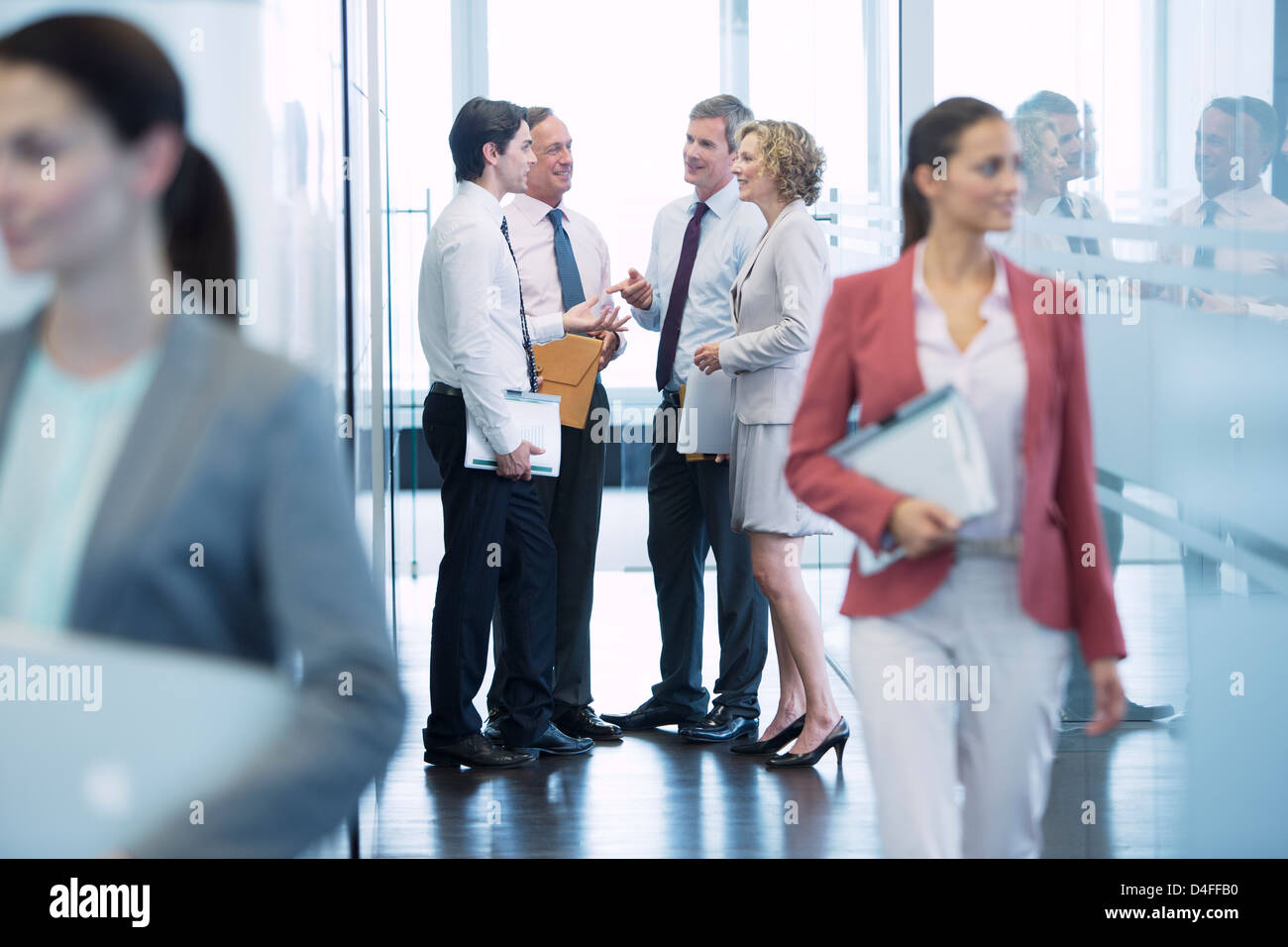 Business people talking in office hallway - Stock Image