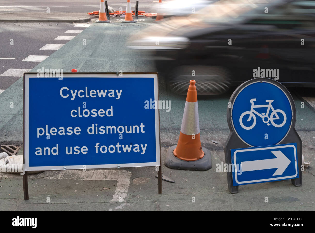 cycleway closed please dismount and use footway sign, with passing blurred motion car, kingston upon thames, surrey, - Stock Image