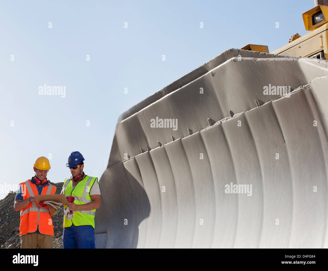 Workers reading blueprints by digger in quarry Stock Photo