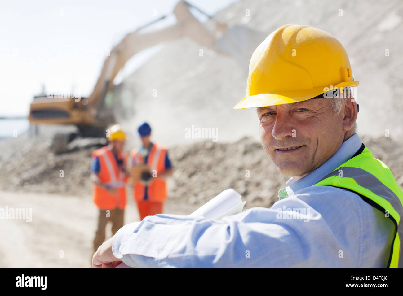 Businessman wearing hard hat in quarry - Stock Image
