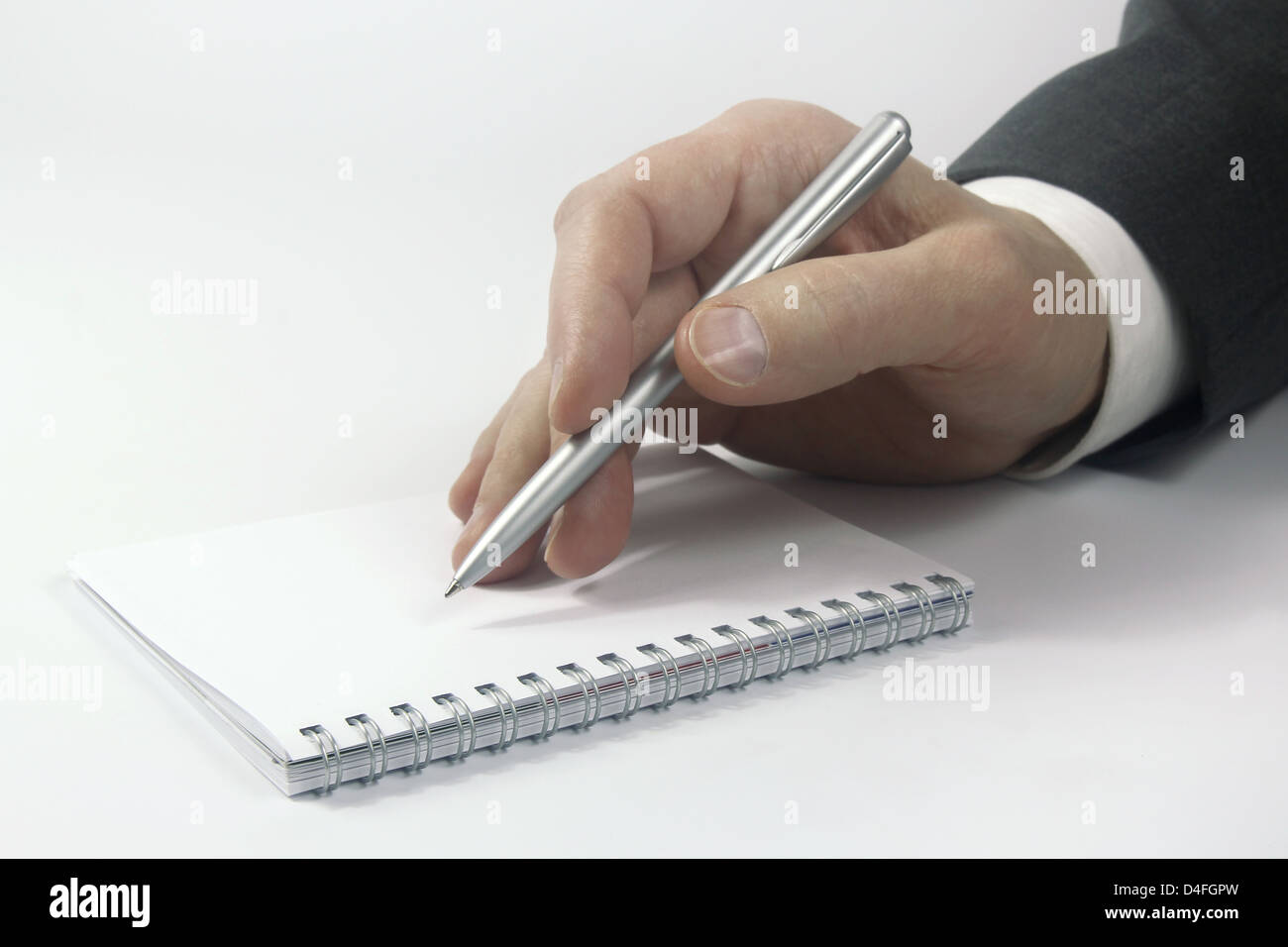 business hand with pen over notebook - Stock Image