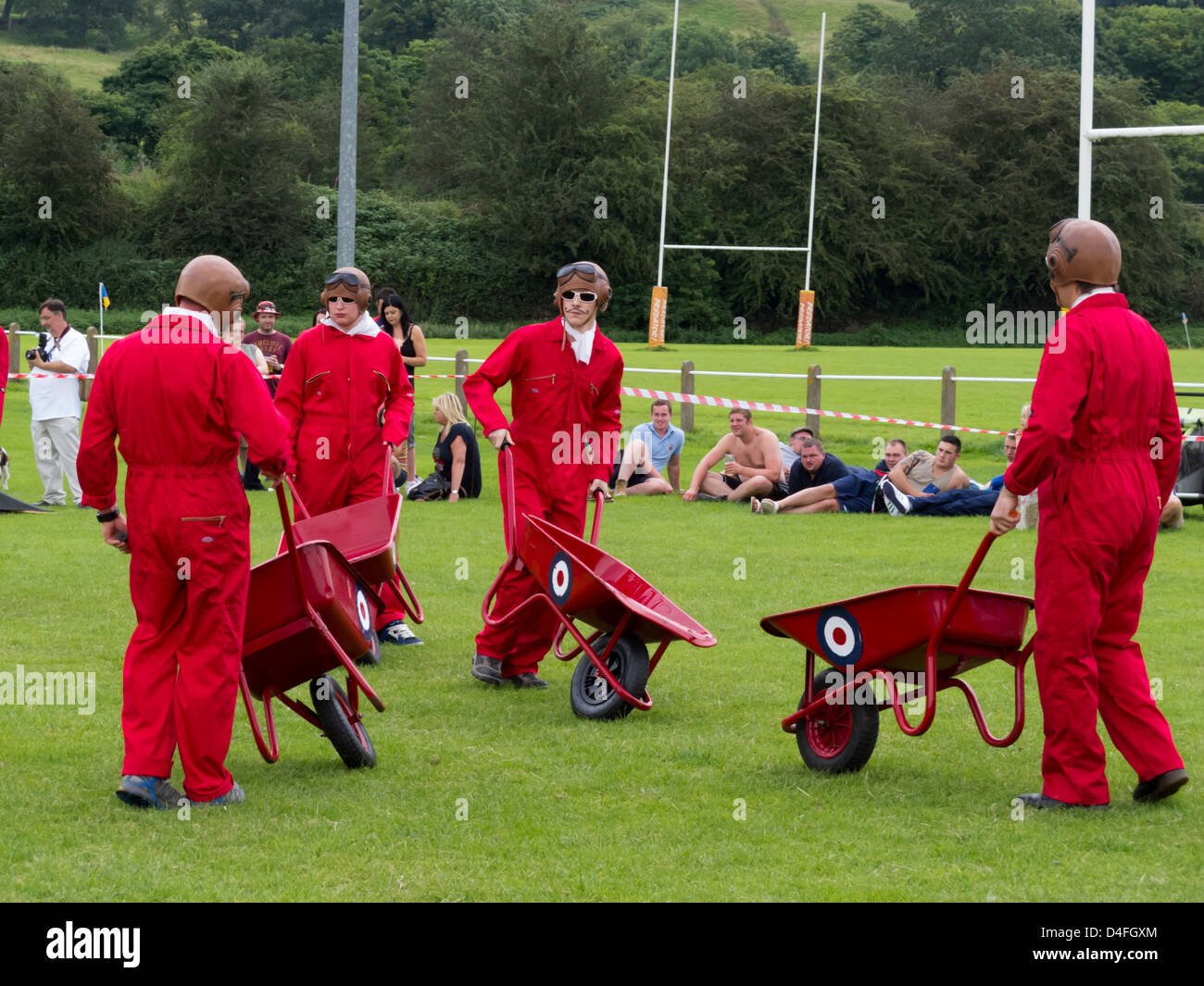 group of men wearing red boiler suits pushing red wheelbarrows round a field at a fete in Derbyshire England - Stock Image