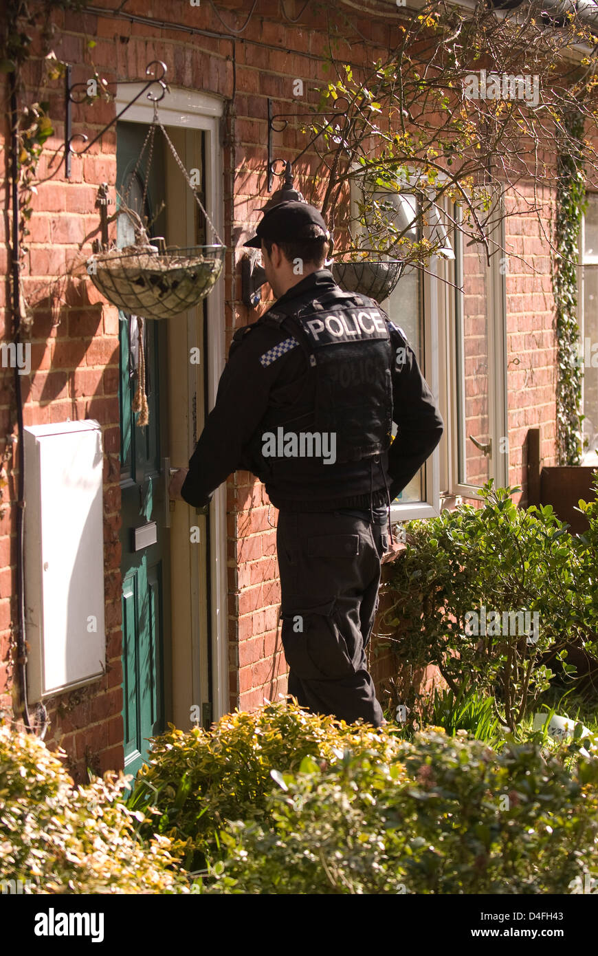 Police officer entering house of suspect who was arrested for threats to kill, Selborne, Hampshire, UK. - Stock Image