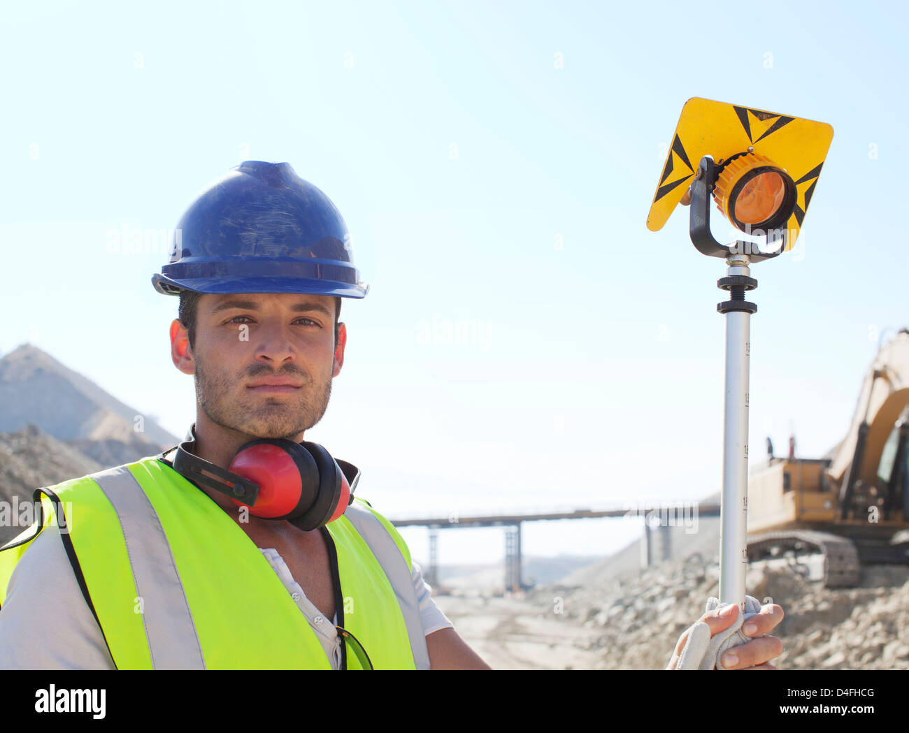 Worker standing in quarry - Stock Image