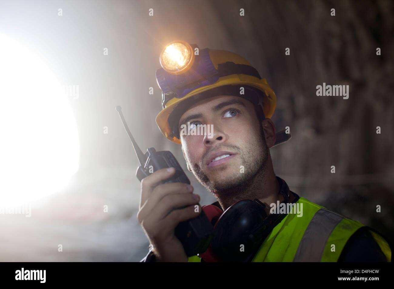 Worker using walkie-talkie in tunnel Stock Photo