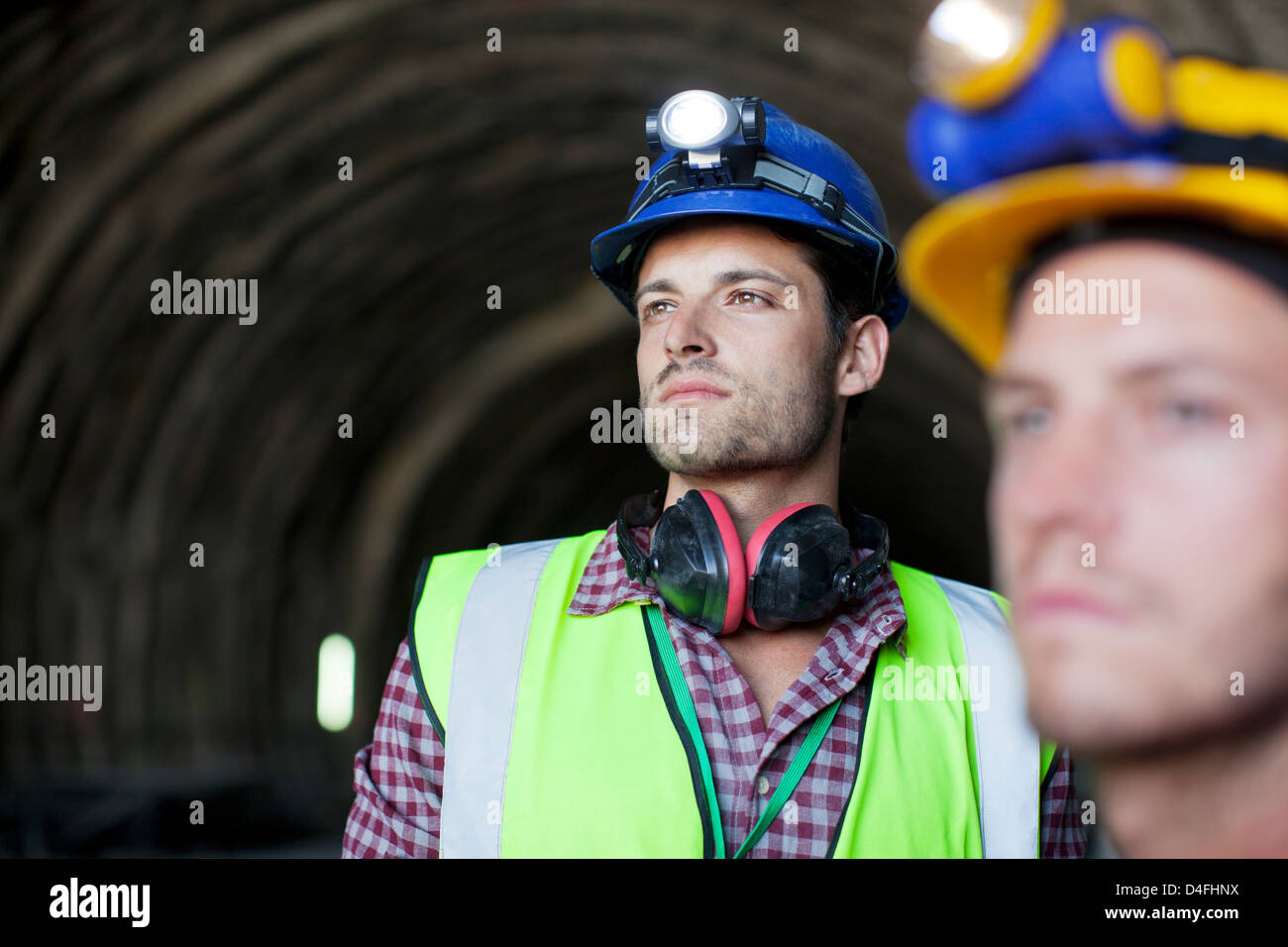 Workers looking out from tunnel Stock Photo