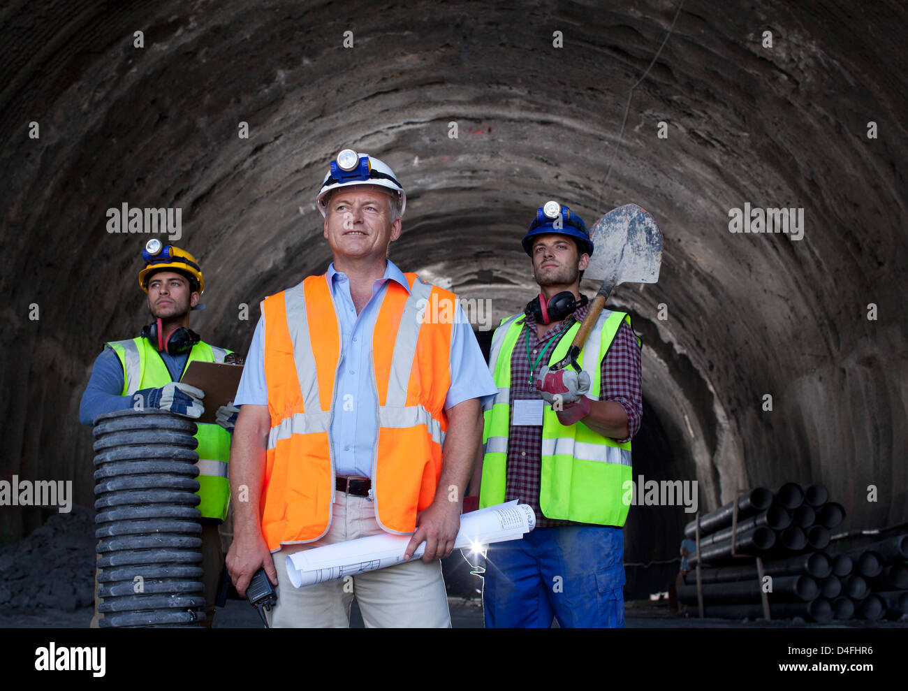 Businessman and workers standing in tunnel Stock Photo