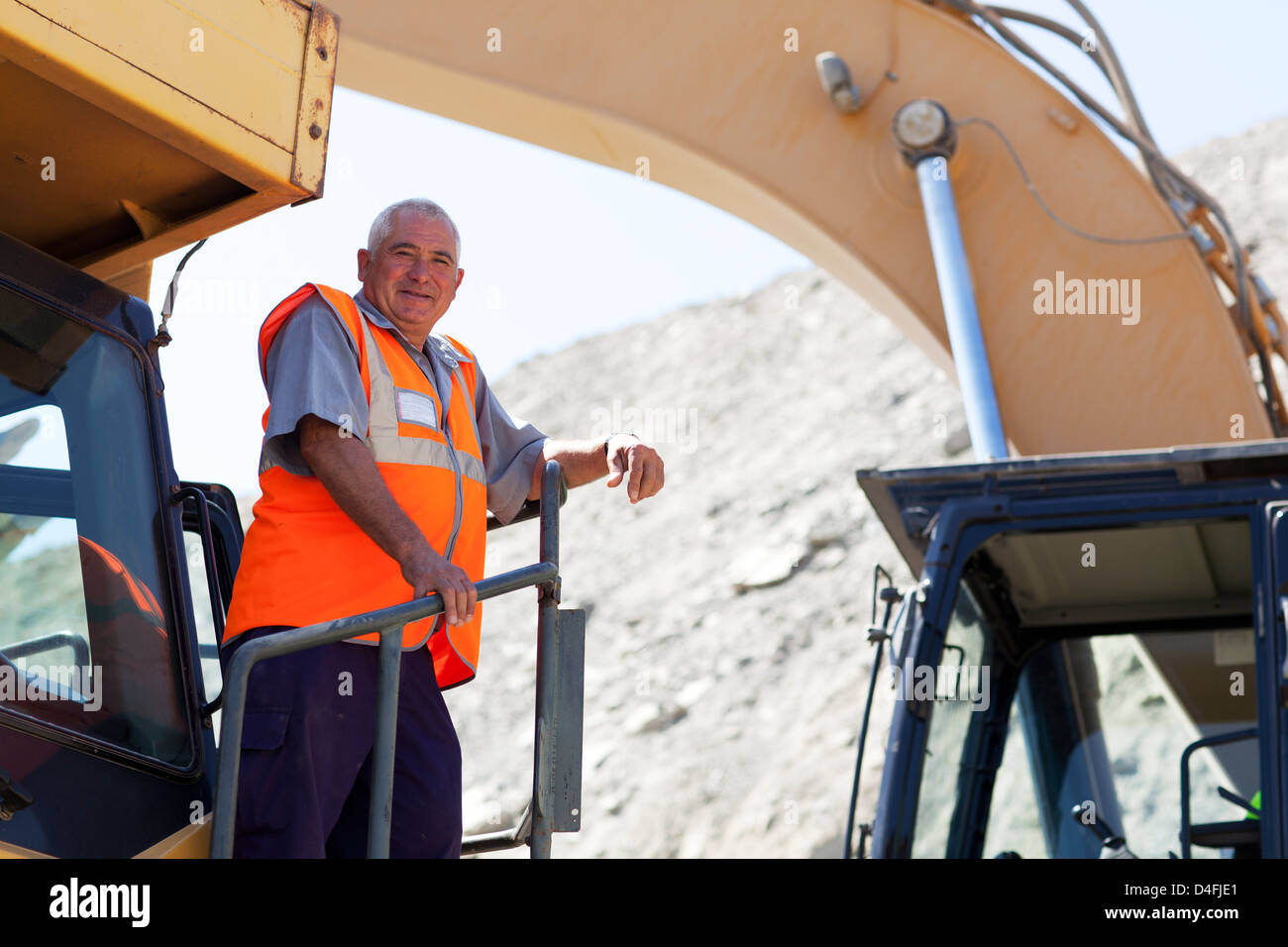 Worker standing on machinery on site - Stock Image