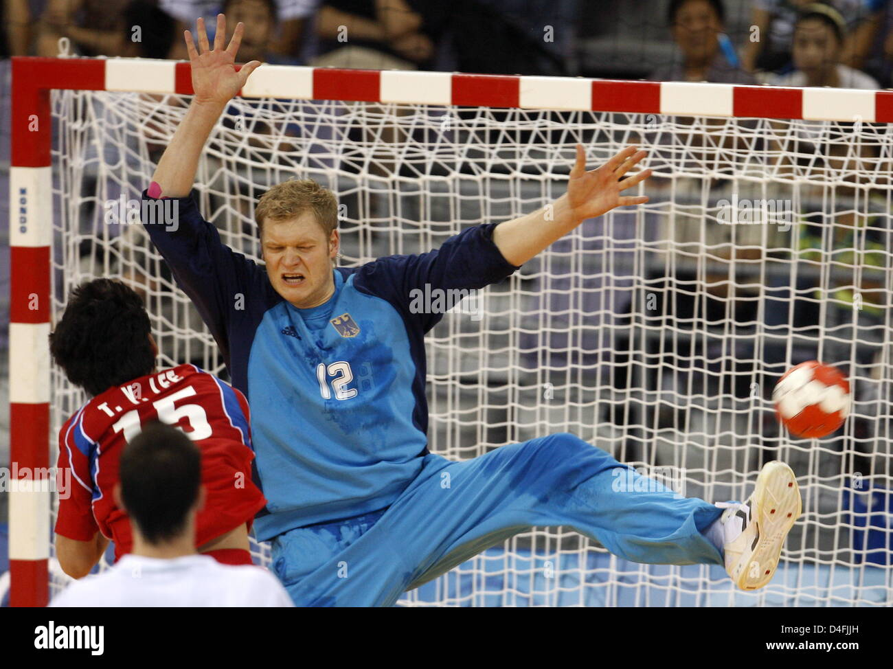 Goalkeeper Johannes Bitter (R) of Germany wards the ball of Teayoung Lee of Korea during the menÒs handball - Stock Image